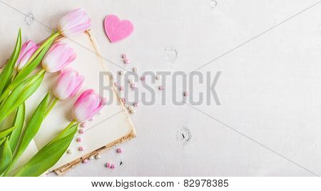 Pink Tulips With Heart And Beads Over White Wooden Table