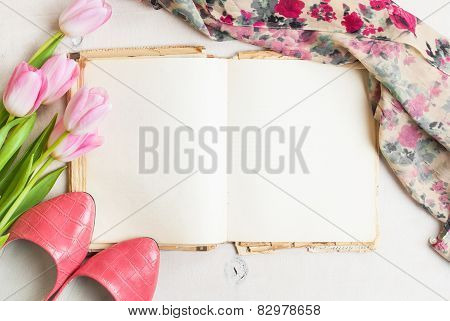 Pink Tulips And Blank Book With Women`s Shoes Over White Wooden Table. Free Space For Text