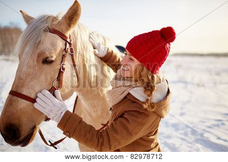 Young female in winterwear looking at horse