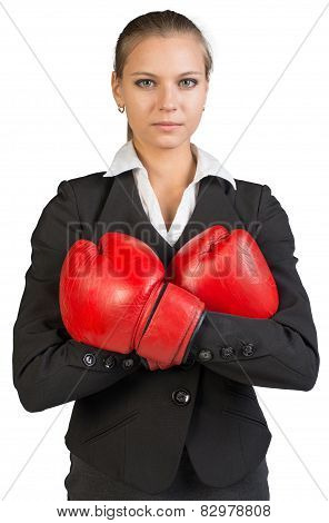 Businesswoman wearing boxing gloves, arms crossed on her breast