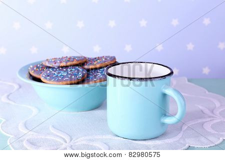 Bowl of glazed cookies and mug of milk on napkin and color dots background