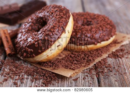 Delicious donuts with icing and chocolate crumb on wooden background