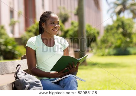 thoughtful african college girl sitting outdoors
