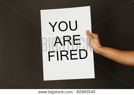 Sheet of paper with text You Are Fired in male hand on dark background