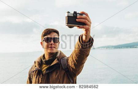 Smiling Man Takes Photographs Self Portrait On Coastline. Focus On Man