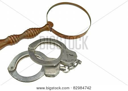 Vintage Magnifying Glass And Handcuffs Isolated