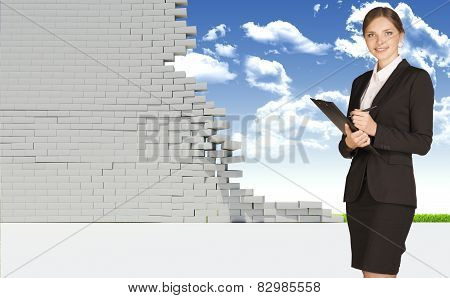 Businesswoman smiling and looking at camera. Dilapidated brick wall, green meadow with sky as backdr