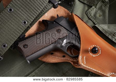 Pistol In Holster And Belt Lie On Military Jacket