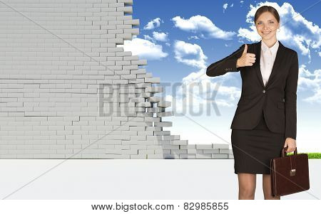 Businesswoman holding suitcase and showing thumb-up. Dilapidated brick wall, green meadow with sky a