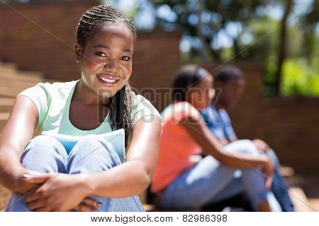 gorgeous afro american college girl sitting outdoors