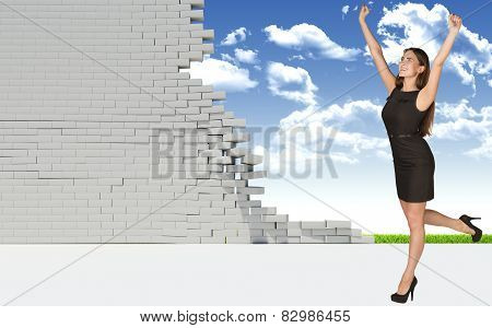 Beautiful businesswoman in dress happily raised his hands up, looking at camera. Dilapidated brick w