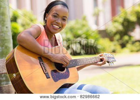 beautiful african american woman playing guitar outdoors