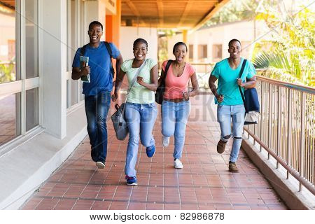 cheerful african college students running to lecture hall