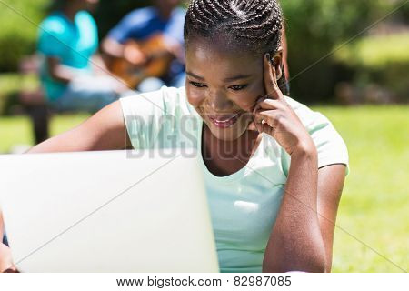 pretty female african college student working on laptop computer