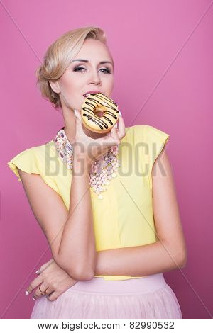 Beautiful blonde women with yellow blouse taste yellow dessert. Fashion shot. Soft colors