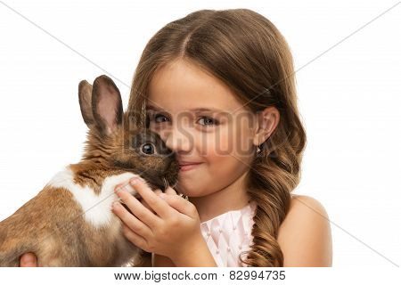 Little girl kissing cute brown bunny
