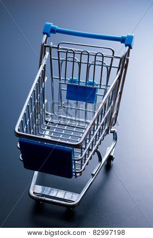 Empty Shopping Cart On Dark Blue Background.
