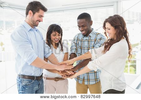 Smiling coworkers joining hands in a circle in the office