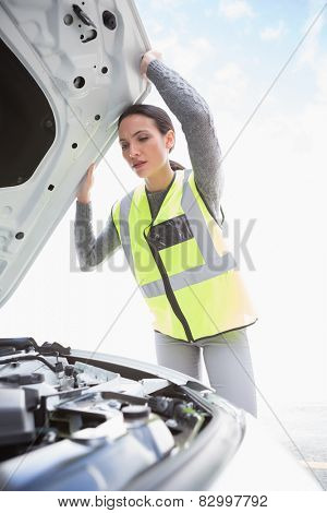 Upset woman checking her car engine in a car park