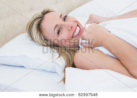 Happy woman lying in bed under duvet at home in the bedroom