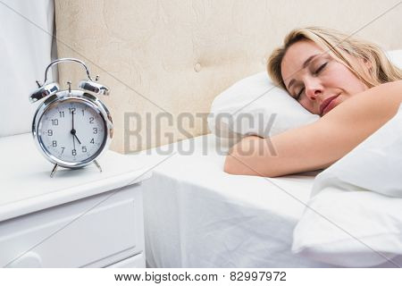 Pretty blonde sleeping in bed with alarm clock on bedside table in the room