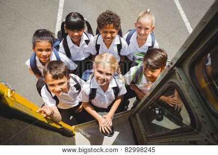 Cute schoolchildren getting on school bus outside the elementary school