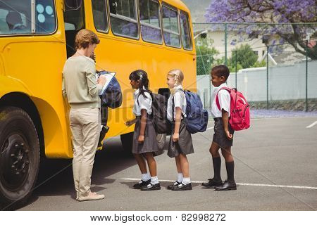 Cute schoolchildren waiting to get on school bus outside the elementary school