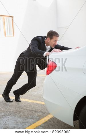Businessman pushing his broken down car in a car park