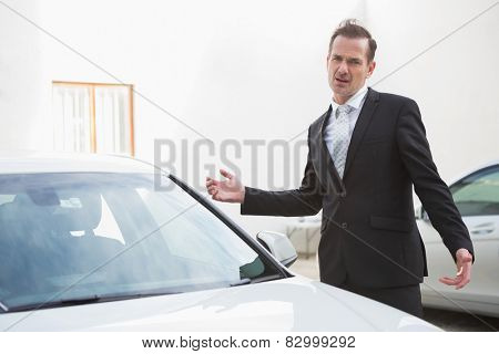 Businessman looking his car engine after breaking down in a car park
