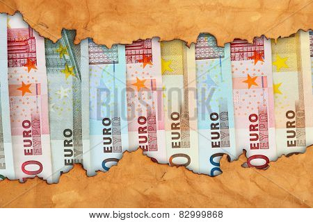 Euro banknotes in torn craft paper frame