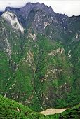 picture of leaping  - vertical vintage style photo of canyon walls in leaping tiger gorge yunnan china with river winding in the canyon and mountains enshrouded with mist