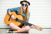 pic of guitar  - Young beautiful trendy girl with acoustic guitar is playing sitting on the floor - JPG