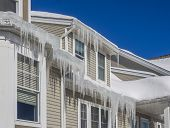 picture of dam  - Ice dams and snow on roof and gutters after bitter cold in New England - JPG