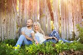picture of wooden fence  - Happy young couple in love hugging  outside next to the wooden fence - JPG