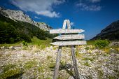 pic of big-foot  - Wooden signpost with three directions on the foot of big mountain - JPG