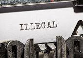 foto of illegal  - Typewriter with white paper page on wooden table - JPG