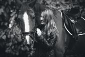 stock photo of hackney  - Closeup black and white portrait of smiling woman walking with horse - JPG