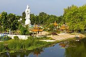 stock photo of stature  - Stature white marble Quan Yin stand near The Bridge of the River Kwai Kanchanaburi Thailand