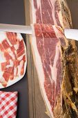 picture of shoulder-blade  - Knife cutting serrano ham slices with plate in the background - JPG