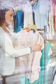 picture of boutique  - Beautiful woman looking through new clothes collection in boutique - JPG