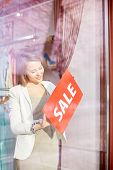 foto of boutique  - Beautiful shop assistant putting sale card on door of boutique - JPG