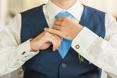 pic of coat tie  - the  groom tieing a tie in the wedding day - JPG