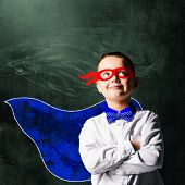 picture of blindfolded man  - school boy wearing a superhero costume with blackboard behind him - JPG