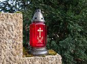image of conifers  - A red grave lantern with golden cross stands on a stone in front of a conifer - JPG