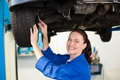 stock photo of garage  - Smiling mechanic adjusting the tire at the repair garage - JPG