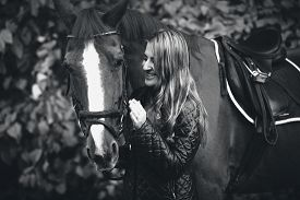 image of hackney  - Closeup black and white portrait of smiling woman walking with horse - JPG