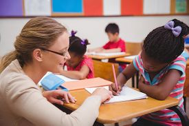 foto of classroom  - Cute pupil getting help from teacher in classroom at the elementary school - JPG