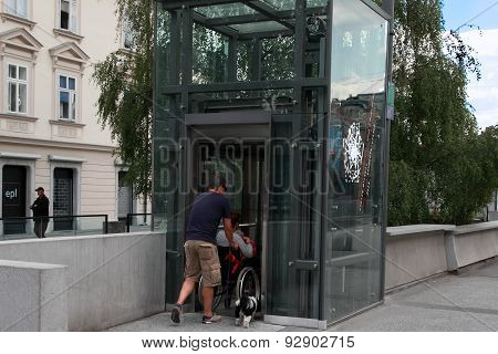 Ljubljana, Slovenia -  June 28, 2014: Husband And Wife In A Wheelchair With A Dog Come In Passenger
