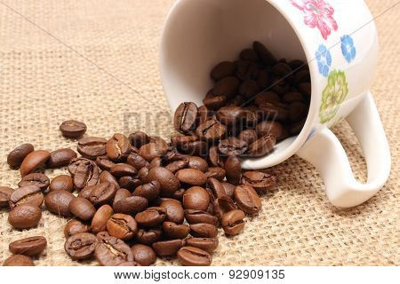 Heap Of Coffee Grains With Overturned Cup