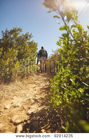 Couple Hiking On Dirt Trial On Mountain
